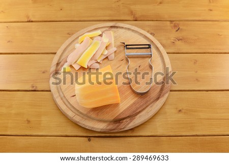 Raw butternut squash being peeled with a vegetable peeler on a wooden chopping board - stock photo