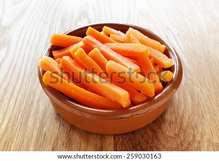 Raw carrot sticks in brown rustic bowl on wooden table - stock photo