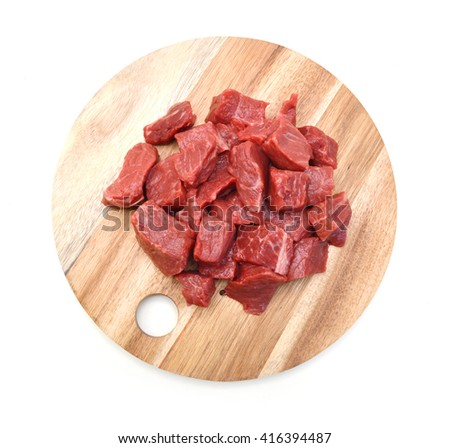 Raw casserole or stewing beef diced. on wooden board on white background  - stock photo