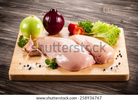 Raw chicken breasts on cutting board - stock photo