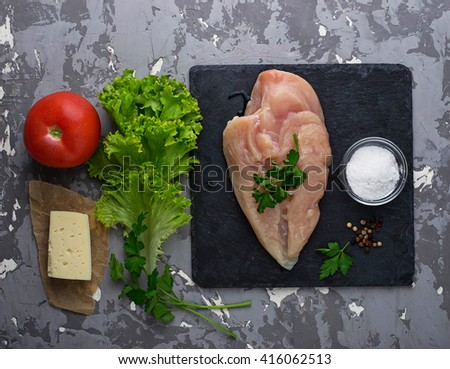 Raw chicken fillet, tomato, cheese and lettuce. Ingredient for salad. Selective focus - stock photo