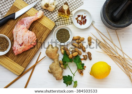 Raw chicken leg with ingredients, to prepare meat skewers with Asian satay peanut sauce, selected focus, narrow depth of field, view from above  - stock photo