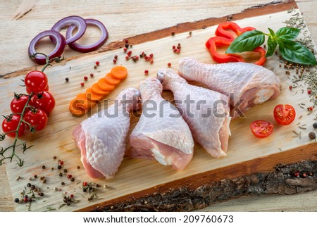 Raw chicken legs on wood, decorated with cherry tomatoes, pepper, onion and basil. - stock photo
