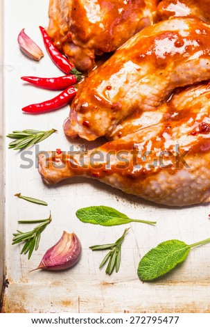raw chicken legs with red spicy sauce with garlic and sage, close up - stock photo