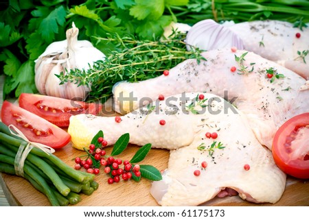 Raw chicken meat portions with fresh seasoning ingredients on wooden board. - stock photo