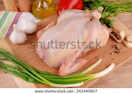 Raw chicken on wooden table - stock photo