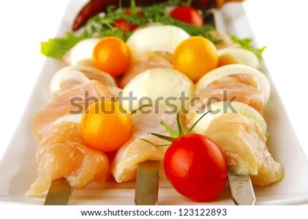raw chicken shish kebab on long white plate - stock photo