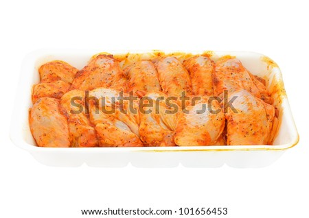 Raw chicken wings marinated in a container isolated on white background - stock photo