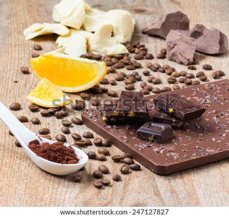 Raw chocolate with orange, cacao and coffee nibs on black background, coconut oil and cocoa mass, selective focus  - stock photo