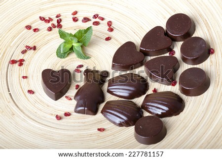 raw chocolates in the shape of bears, hearts, seashells on a wooden plate - stock photo