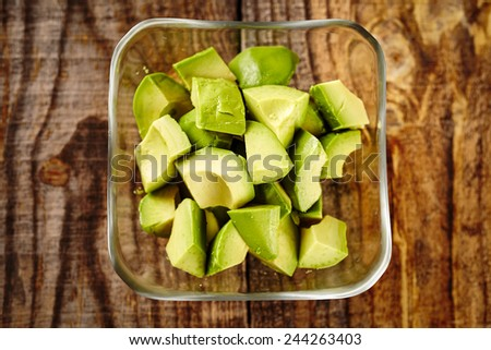 Raw chopped avocado on a wooden board - stock photo