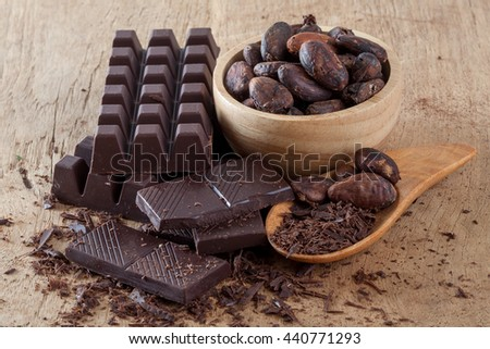 Raw cocoa beans, chocolate on wood background - stock photo