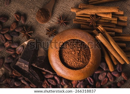 Raw cocoa beans, raw dark  homemade chocolate for rawfoodists, cinnamon sticks, star anise and cocoa powder in a wooden bowl, top view - stock photo