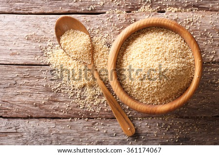 Raw Couscous in a wooden bowl and spoon on the table. Horizontal top view