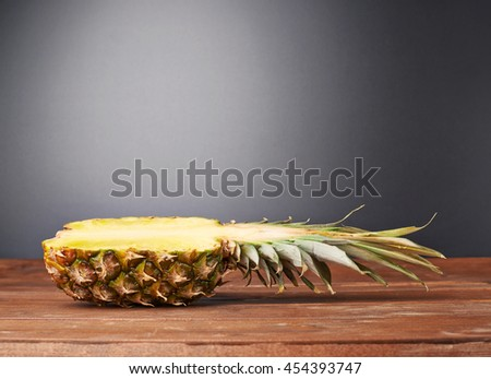 Raw cut pineapple on wooden brown surface table - stock photo