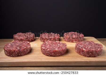 Raw cutlet of minced meat on a wooden cutting board on black background. - stock photo