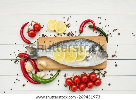 Raw dorado fish with lemon on wooden cutting board - stock photo