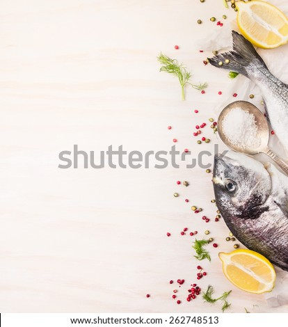 Raw  dorado fish with multicolor pepper,lemon an spoon of salt on white wooden background, top view, place for text - stock photo