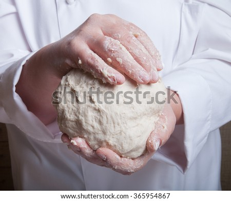Raw dough in a chef hands. - stock photo