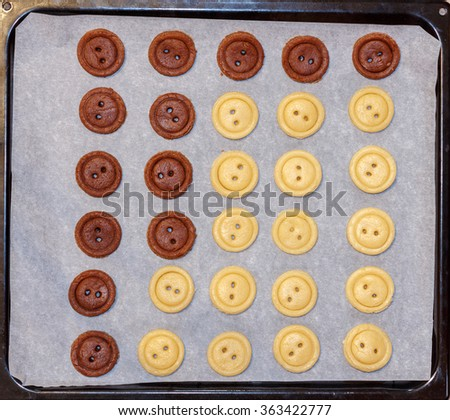 Raw dough. Yellow and brown cookies buttons on sheet pan. Cooking. - stock photo