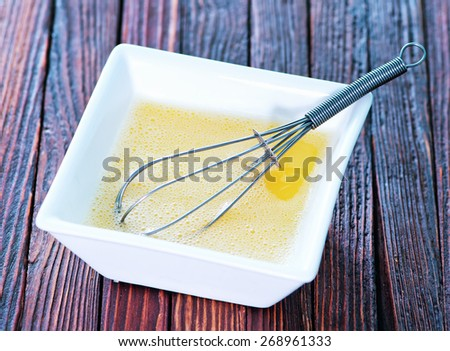raw egg and whisk in white bowl - stock photo