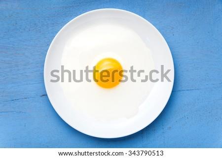 raw egg yolk on the dish on table - stock photo