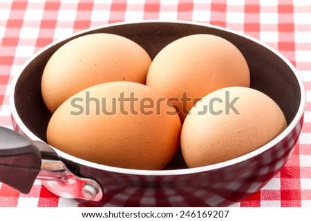 raw eggs in frying pan   - stock photo