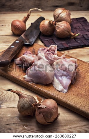raw fillet chicken meat and onions in the process of cooking food - stock photo
