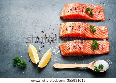 Raw Fillet of salmon with sea salt and pepper. Fresh fish. Top view, copy space. Food background. - stock photo
