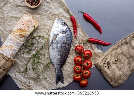 Raw fish , herbs and spices on cutting board , top view. Healthy food or diet nutrition concept. - stock photo