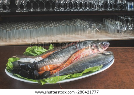 Raw fish in restaurant. Cups in the background - stock photo
