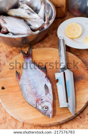 raw fish on wooden cutting board with knife in the kitchen - stock photo