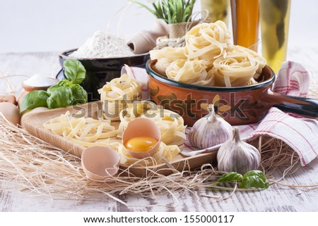 Raw food composition - yellow tagliatelle in a clay pot with a flour and eggs  placed on a wooden tray on a bright background. - stock photo
