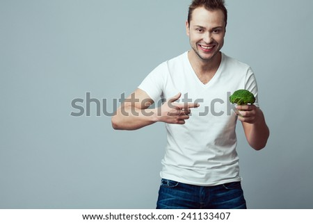 Raw food concept. Smiling good looking boy in casual clothing holding broccoli, pointing on it with right index finger over gray background. Healthy skin, bristle face. Copy-space. Studio shot - stock photo