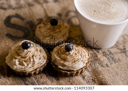 raw food cupcakes with nutcream and blueberry on top in front of a white cup of coffee, vegan ingredients only - stock photo