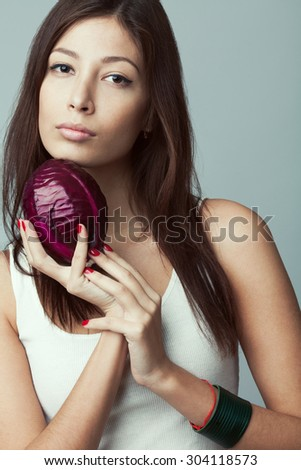 Raw food, veggie concept. Portrait of smiling good looking girl in casual clothing holding red cabbage in her hands over gray background. Healthy skin, glossy brown hair. Closeup. Studio shot - stock photo