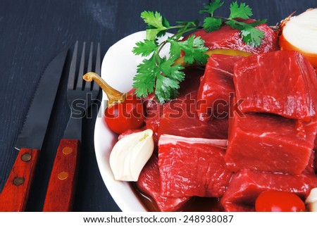raw fresh beef meat slices in a white bowls with onion and red peppers serving on blue table with cutlery - stock photo