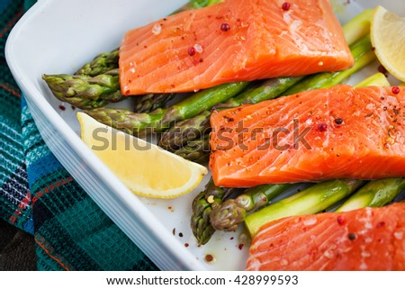 Raw fresh delicious salmon, green asparagus and lemon in pan, ready to cook - stock photo
