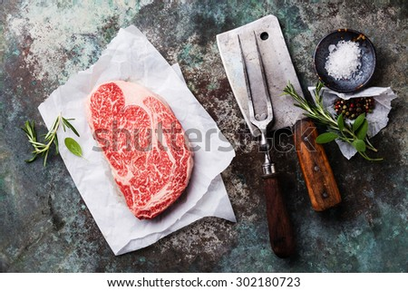 Raw fresh marbled meat Black Angus Steak, seasonings, meat fork and cleaver on metal background - stock photo