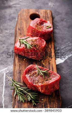 Raw fresh marbled meat Steak filet mignon and seasoning on dark marble background - stock photo