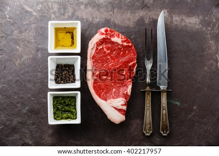 Raw fresh marbled meat Steak Striploin and seasoning on stone slate background - stock photo