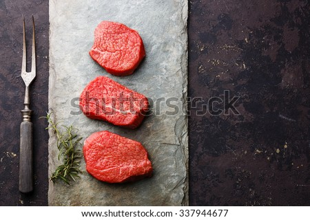 Raw fresh marbled meat Steaks and meat fork on stone slate on dark background - stock photo