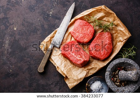 Raw fresh marbled meat Steaks with seasonings and kitchen knife on dark background - stock photo