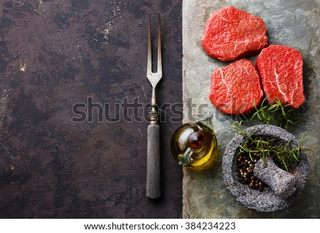 Raw fresh marbled meat Steaks with seasonings and meat fork on stone slate on dark background - stock photo