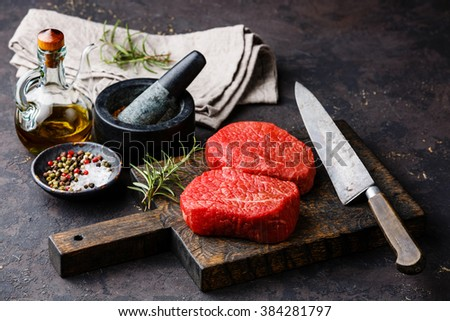 Raw fresh marbled meat Steaks with seasonings on dark background - stock photo