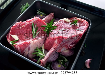 Raw fresh meat beef steak, seasonings with salt, pepper, rosemary leaves and red onion, on a black tray ready to be cooked - stock photo