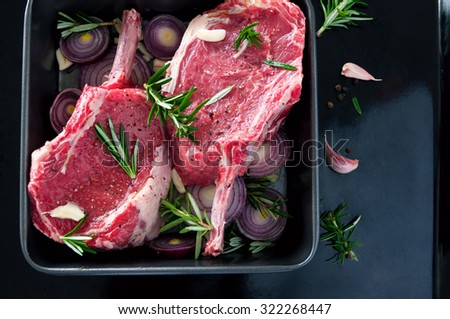 Raw fresh meat beef steak, seasonings with salt, pepper, rosemary leaves and red onion, on a black tray ready to be cooked, top view, copy space, flat layout - stock photo