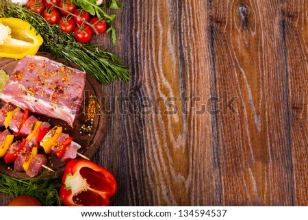 Raw fresh meat on cutting board with condiments and fresh vegetables - stock photo