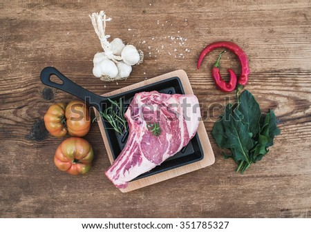 Raw fresh meat rib eye steak with pepper, salt, chili, garlic, spinach, heirloom tomatoes and rosemary in cooking pan over rustic wooden background, top view - stock photo