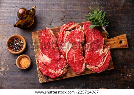 Raw fresh meat Ribeye steak entrecote and seasoning on dark wooden background  - stock photo